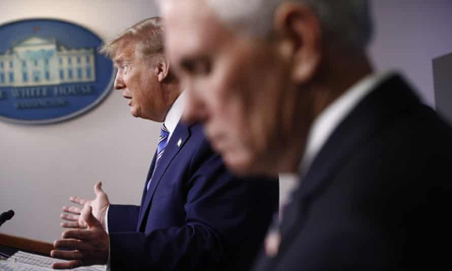 Mike Pence listens as Donald Trump speaks during a coronavirus task force briefing at the White House.
