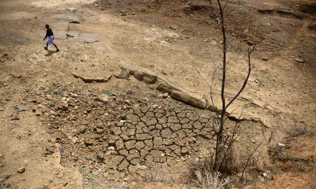 An Indian farmer walks across the bed of a pond that has dried out during a water crisis.