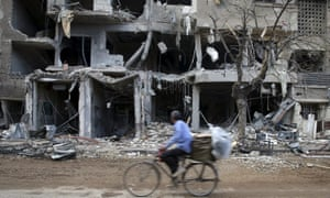 A man rides a bicycle near damaged buildings in Jobar, a suburb of Damascus, Syria.