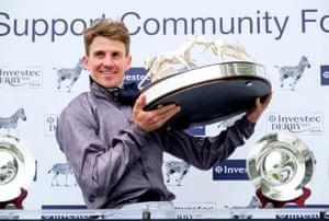 Jockey Emmet McNamara lifts the trophy as he celebrates winning the Derby on Serpentine.