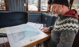 Sigurdur Jonsson looks at maps on his boat, the Aurora.