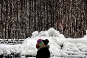 Atlanta, GAA child walks past as ice builds up along a downtown water fountain in the state capital. A brutal winter storm scattered a wintry mix of snow, sleet and freezing rain from normally balmy north Florida up the Southeast seaboard Wednesday, adding to the misery of a bitter cold snap.