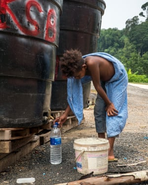 Boy in blue sarong fills bottle from graffitied tank.