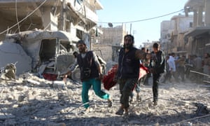 Syrian volunteers carry an injured person
