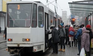 Passengers board a public transport tram at a stop in downtown Tallinn