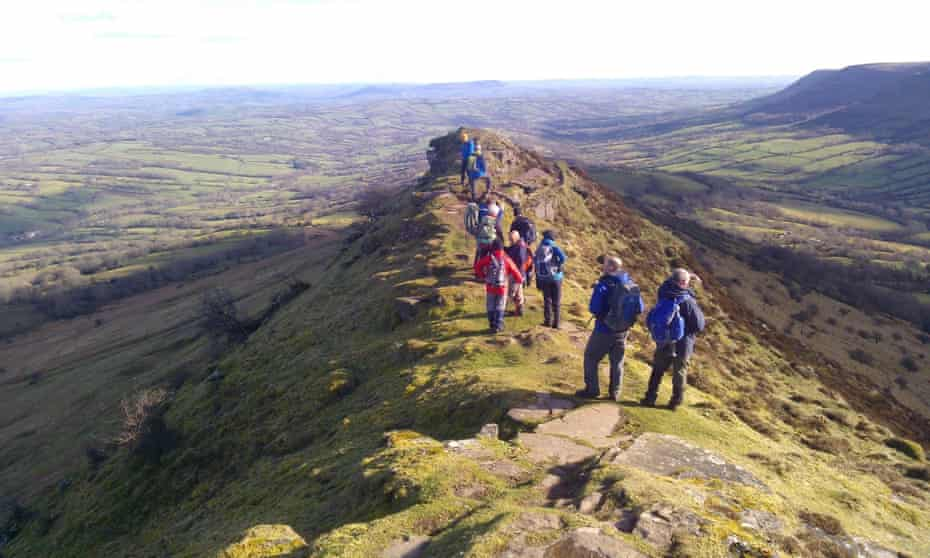 hikers on Crug Hywel, with a view south over Crickhowell.