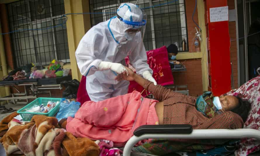 Nepalese paramedics treat a Covid-19 patient outside a hospital in Kathmandu, Nepal.
