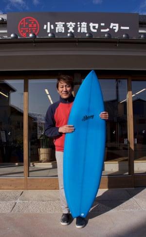 Shinji Murohara stands outside his newly opened surf shop near the Fukushima coast