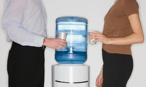 Two office workers talk over a water cooler