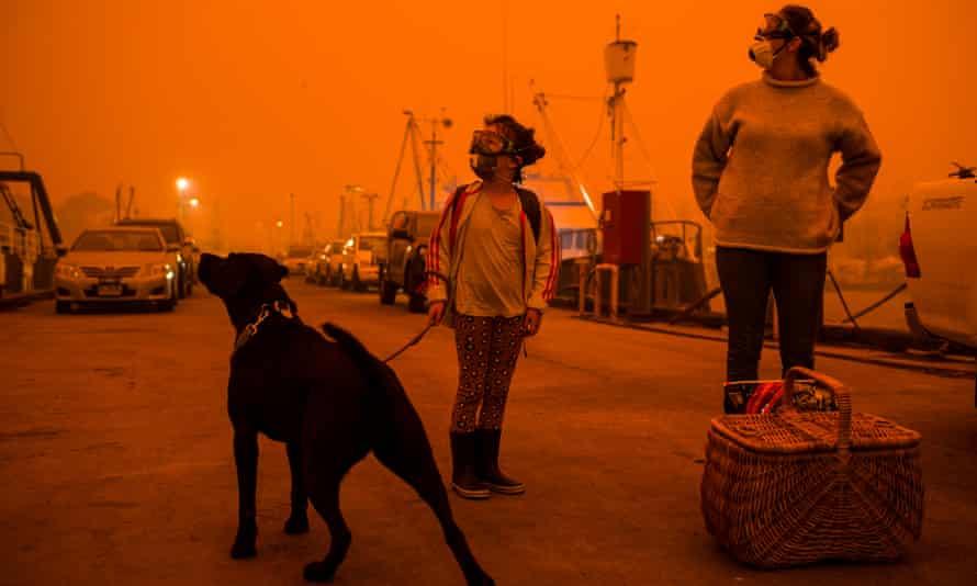 people standing under orange skies during bushfires