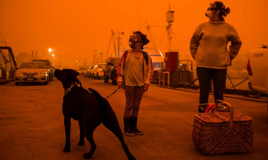 Eden residents prepare to take shelter aboard a tug boat at the town's wharf as a bushfires threatened the town on Sunday.