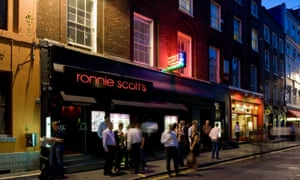 Nighttime, and a view of the outside of famous London jazz club Ronnie Scott's. People mill around outside, caught in the neon signs.