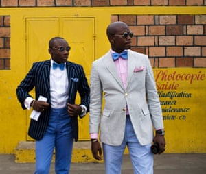 Two men in the Congo in trim sapeur suits with bow ties