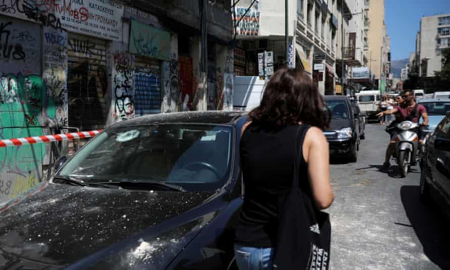 A woman walks on a street past a damaged car after an earthquake near Athens, Greece