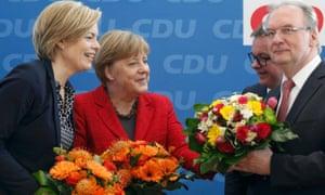 Angela Merkel  presents flowers to   Reiner Haseloff, Guido Wolf and Julia Klöckner  on Monday