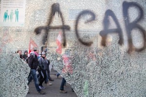 Protestors pass a smashed bus stop with graffiti reading ACAB ( All coppers are bastards)