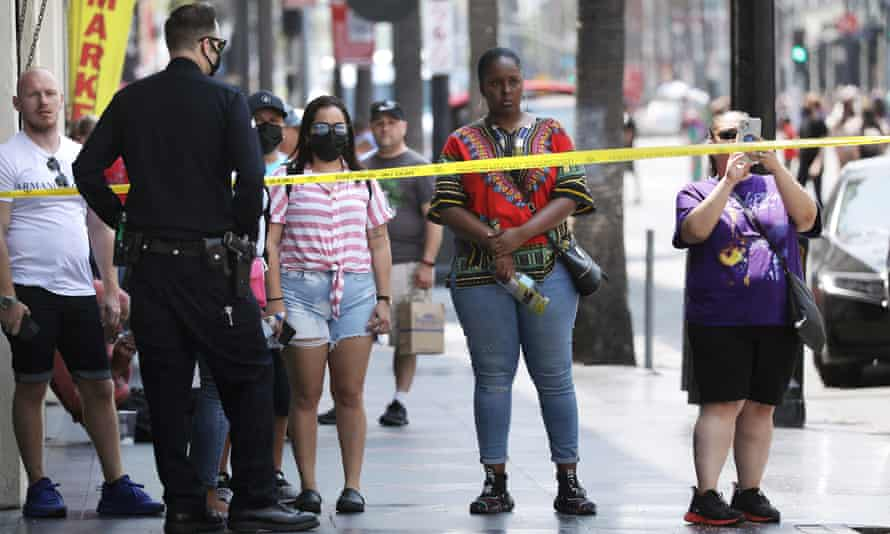 A police officer behind yellow caution tape stops pedestrians at the intersection of Hollywood Boulevard and Highland Avenue in Los Angeles.