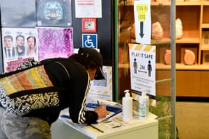 A customer signs contract tracing form before entering a store in Wellington, New Zealand.