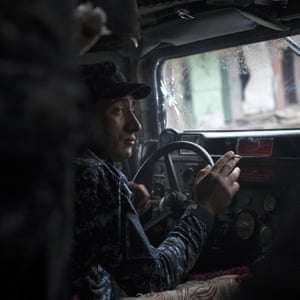 An Iraqi federal policeman drives a humvee during fighting in western Mosul. March 13