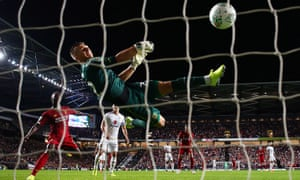 MK Dons goalkeeper Stuart Moore cannot hold James Milner's shot to give Liverpool the lead in the Carabao Cup tie.
