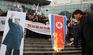 A South Korean protester burns a North Korean flag in opposition to the North's participation in the Pyeongchang Winter Olympics.