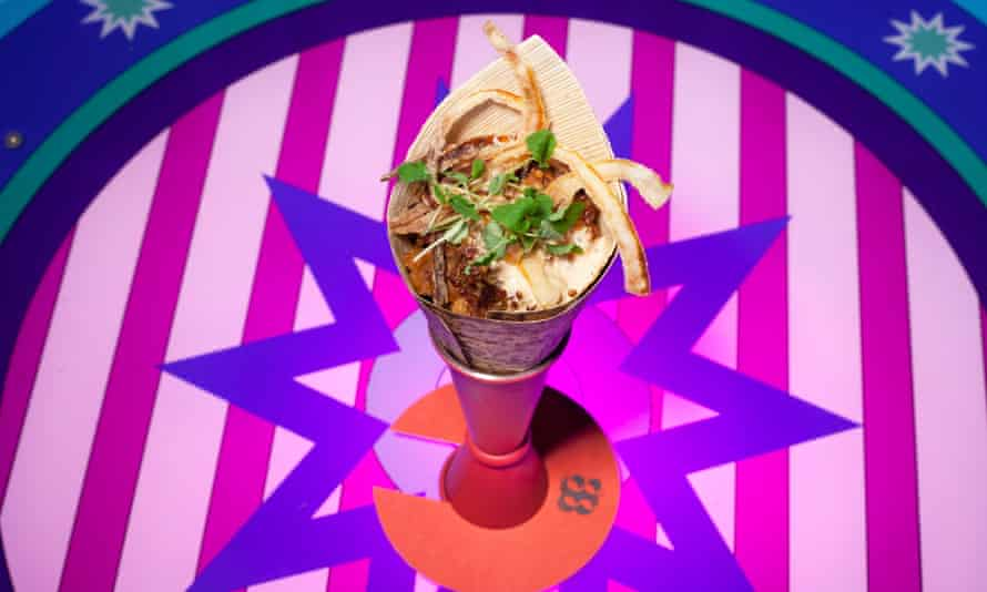 A cone of food on a bright-coloured stripy background
