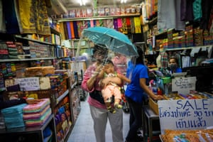 A woman carries a baby under an umbrella with a plastic at a market in Bangkok, Thailand