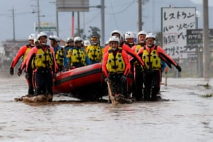 Rescue workers carry a rubber dinghy as they search a flooded area in the aftermath of Typhoon Hagibis, which caused severe floods at the Chikuma River in Nagano Prefecture.