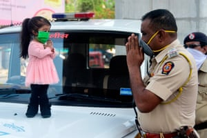 Jyoti Amge greets a police officer during her campaign supporting the lockdown of 1.3 billion Indians