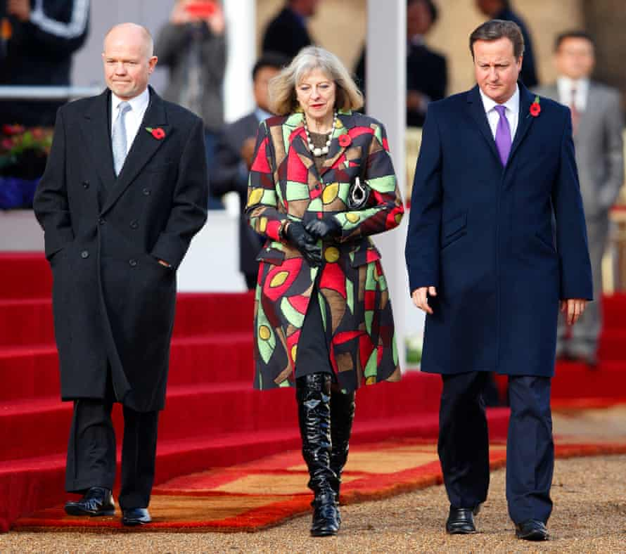 Theresa May pulls of some over-the-knee boots at a public occasion.