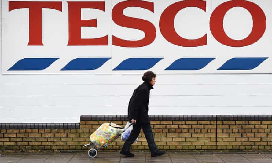 a woman passes a huge tesco sign