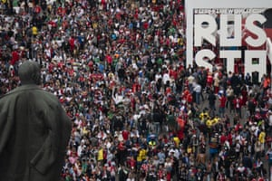 Fans stream past the statue of Lenin as they make their way into Luzhniki stadium