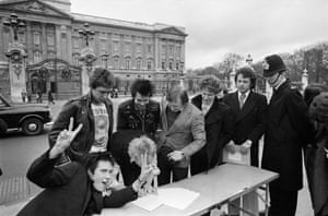 The Sex Pistols, are about to be moved by a policeman as they sign a copy of their new recording contract with A & M Records outside Buckingham Palace.