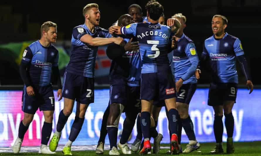 Wycombe's players celebrate with Adebayo Akinfenwa after his dramatic injury-time winner.