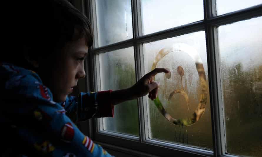 A boy draws a sad face on a steamy window