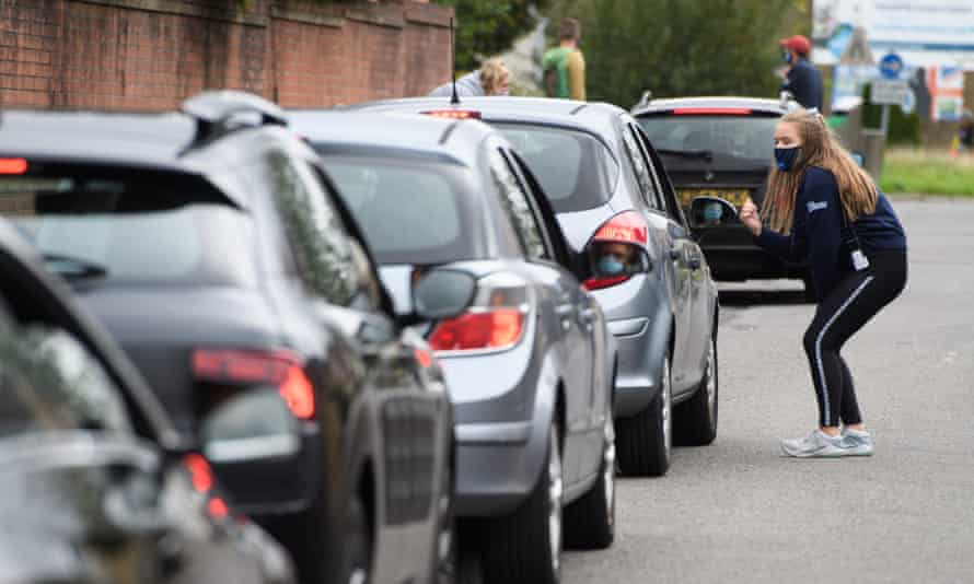 People queue in their cars as they wait outside the Covid-19 testing centre in Caerphilly, Wales.