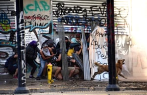 A dog barks as demonstrators cover themselves against water cannons used on them by riot police during clashes in Santiago.