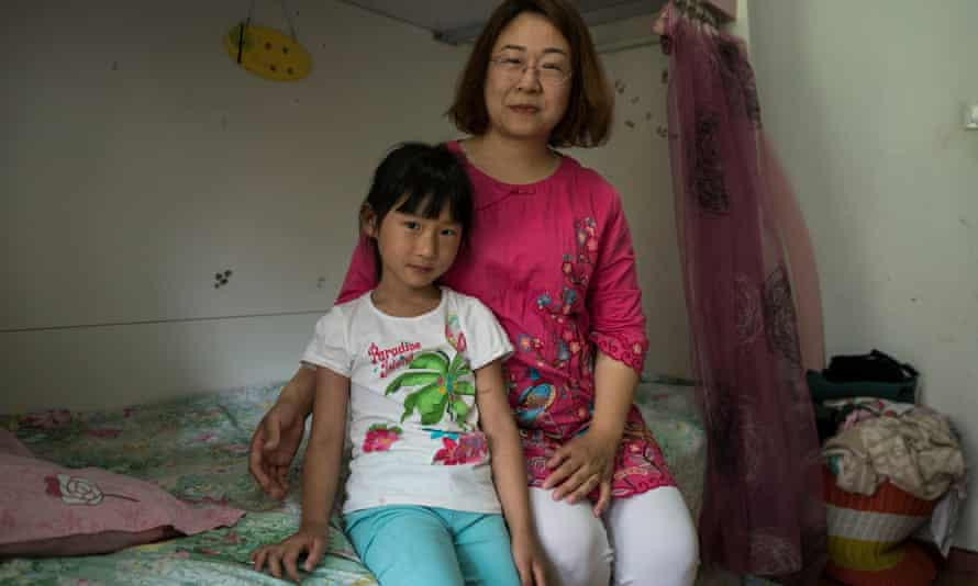Li Jiamei poses for a portrait with her mother Wang Qiaoling in her bedroom at home in Beijing.