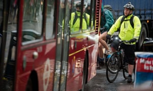 Cyclist by a bus in traffic