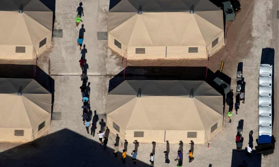 Immigrant children are led by staff in single file between tents at a detention facility next to the Mexican border in Tornillo, Texas on 18 June 2018.