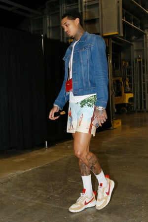 Jordan Clarkson in shorts, trainers and a denim jacket with a tiny red bag around his neck, walking through an airport