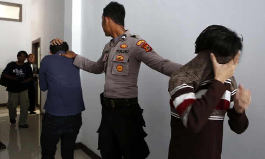 Two men on trial for being in a same-sex relationship are escorted to the courtroom at the Sharia court in Banda Aceh, Indonesia. Police in Jakarta have now arrested 141 men for a party at an alleged gay sauna.