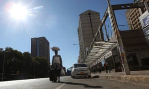 A woman walks along an empty street in the central business district of Harare during the shutdown