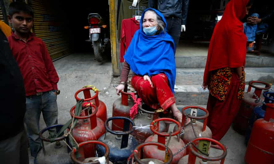 A Nepalese woman waits for a refill of her cooking gas cylinders, in Kathmandu