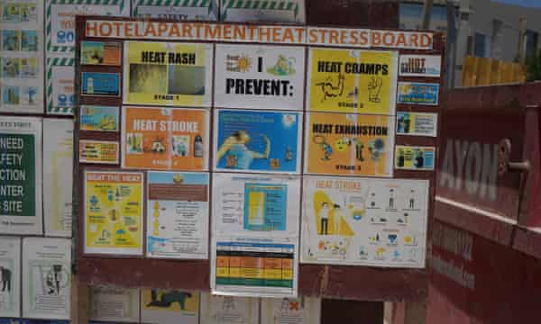 Signs warn of heat stress on a construction site in Doha.