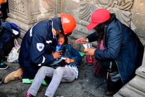 Rescue personal assist a young girl after police fired tear gas to break up the procession.