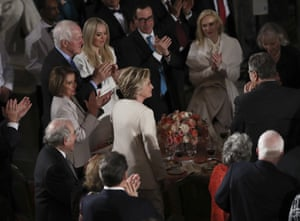 Hillary Clinton stands and is applauded after being lauded by Donald Trump during his speech at the inaugural luncheon.