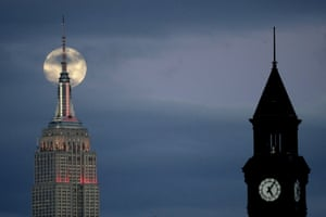 The moon is seen in its waxing gibbous stage behind the Empire State Building, left, with the Lackawanna rail and ferry station tower seen at right, from Jersey City, New Jersey, US