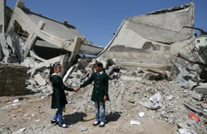 Shaima, 10, and a classmate beside a destroyed part of Shuje'iyah Girls' School