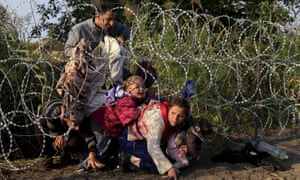 Syrian migrants cross under a fence as they enter Hungary at the border with Serbia.